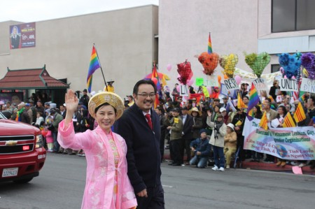 Garden Grove Councilwoman Dina Nguyen, accompanied  by her husband Joseph Dovinh, waves to the crowds at 2013 Tet Parade in Westminster
